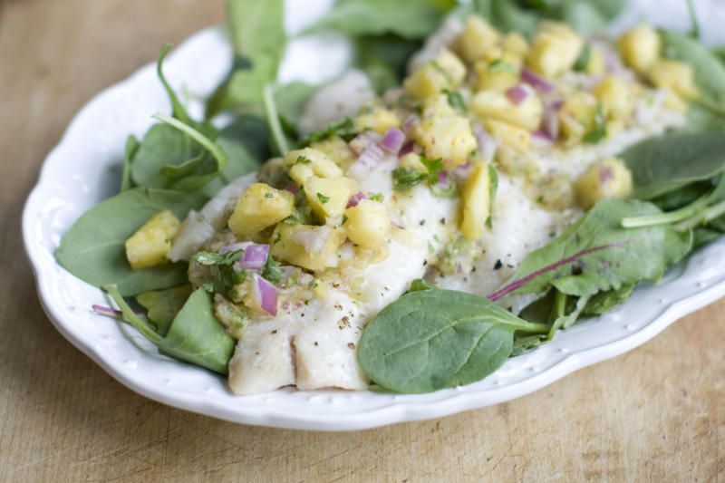 This Dec. 2, 2013 photo shows baked haddock with pineapple mint salsa in Concord, N.H. Baked white fish is a fast and healthy way to get dinner on the table. The secret to getting a good tasting baked white fish, without adding tons of fat and calories or rendering it a tasteless hunk of protein, is all in how you dress it. (AP Photo/Matthew Mead)