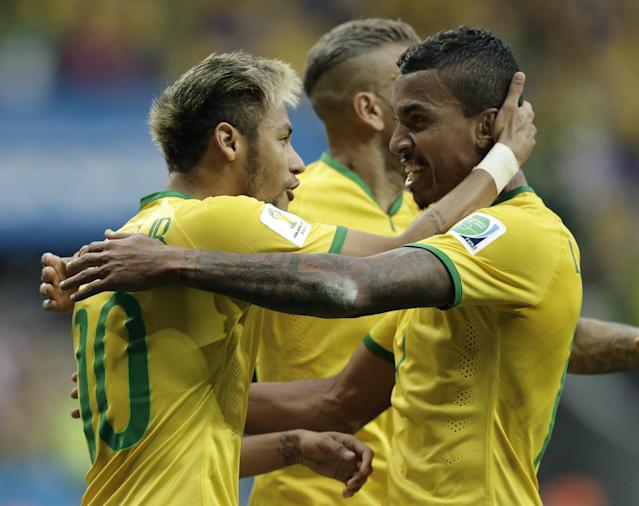 Brazil's Neymar celebrates with Brazil's Luiz Gustavo, right, after scoring his side's first goal during the group A World Cup soccer match between Cameroon and Brazil at the Estadio Nacional in Brasilia, Brazil, Monday, June 23, 2014. (AP Photo/Bernat Armangue)