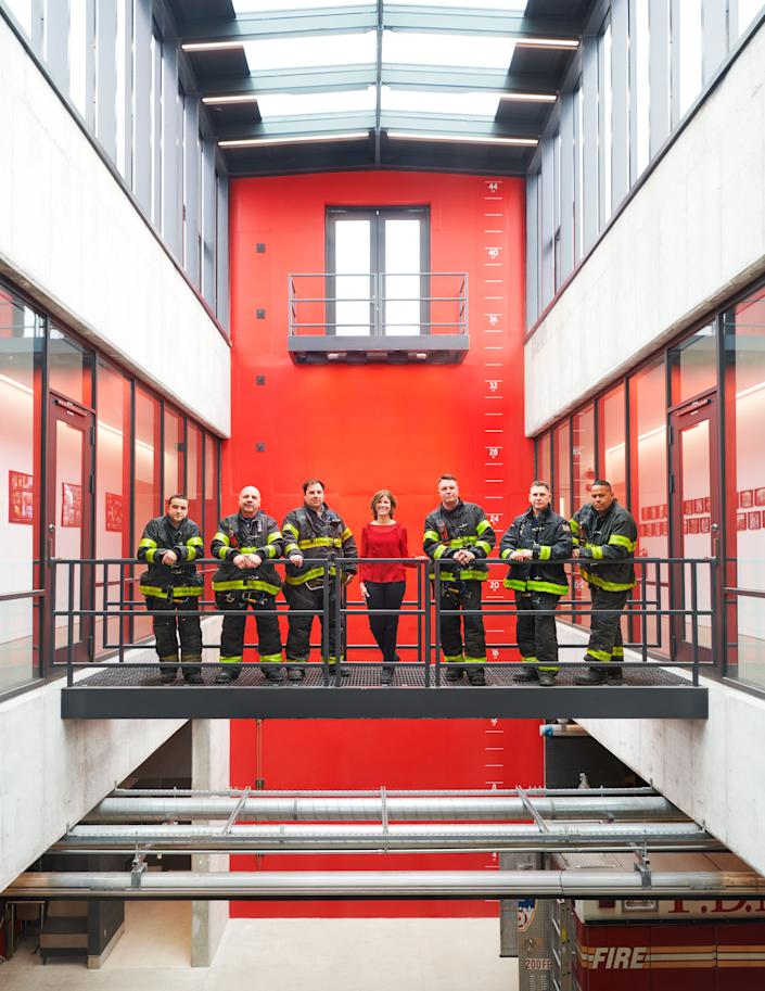 "<div class=""caption""> Gang poses in the atrium with rescue workers; the climbing wall and balcony at rear are used to simulate missions. </div>"