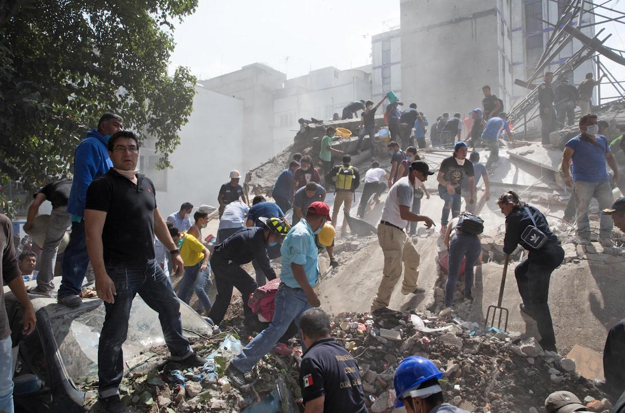 <p>People hunt through the rubble for any survivors trapped in the wreckage (Rex features) </p>