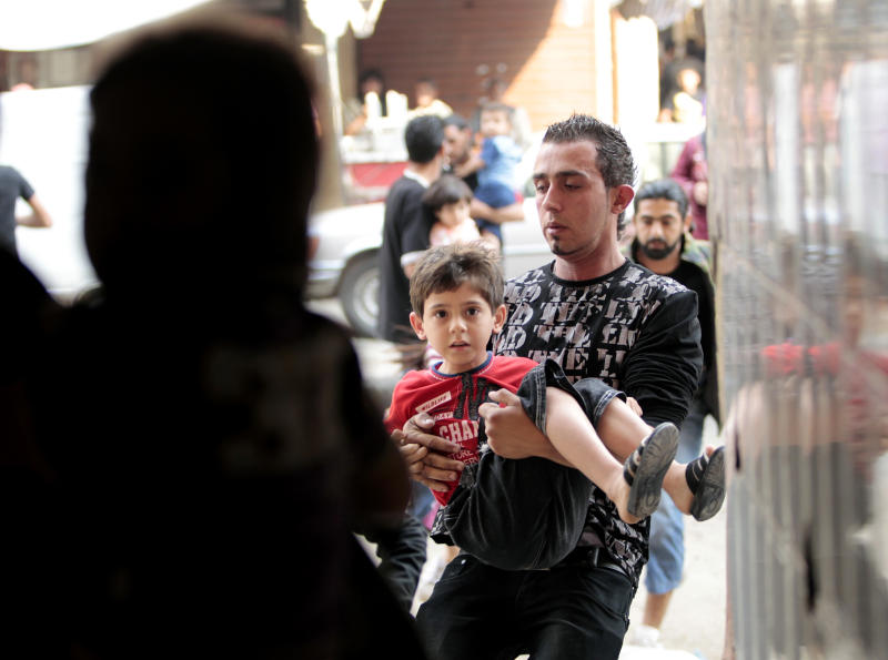 A Sunni man, holds his son as they flee their house during clashes, in the northern port city of Tripoli, Lebanon, Sunday May 13, 2012. Sectarian violence linked to the unrest in neighboring Syria shook the northern Lebanese city of Tripoli on Sunday, with street clashes killing one soldier and two civilians, the state news agency said. Residents said running gun battles broke out in the city Saturday and continued through the night primarily between a neighborhood populated by Sunni Muslims opposed to Syrian President Bashar Assad and another area with many Assad backers from his Alawite sect. (AP Photo/Hussein Malla)