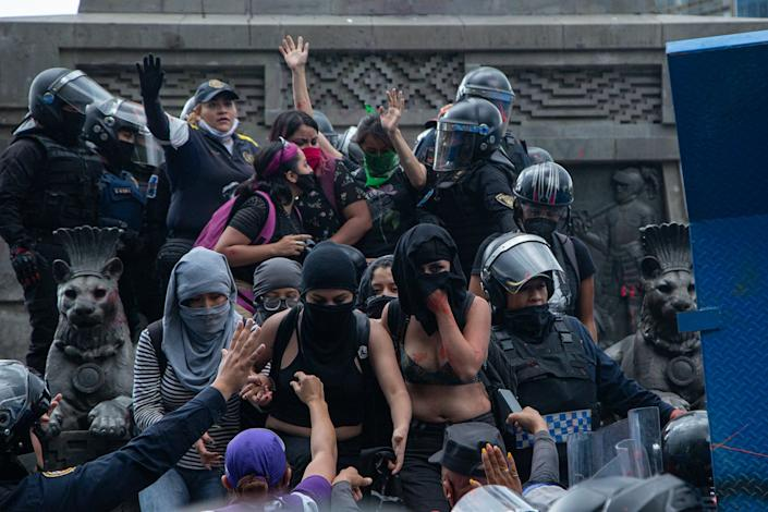 Women dressed in black and wearing face masks clash with police in Mexico CIty
