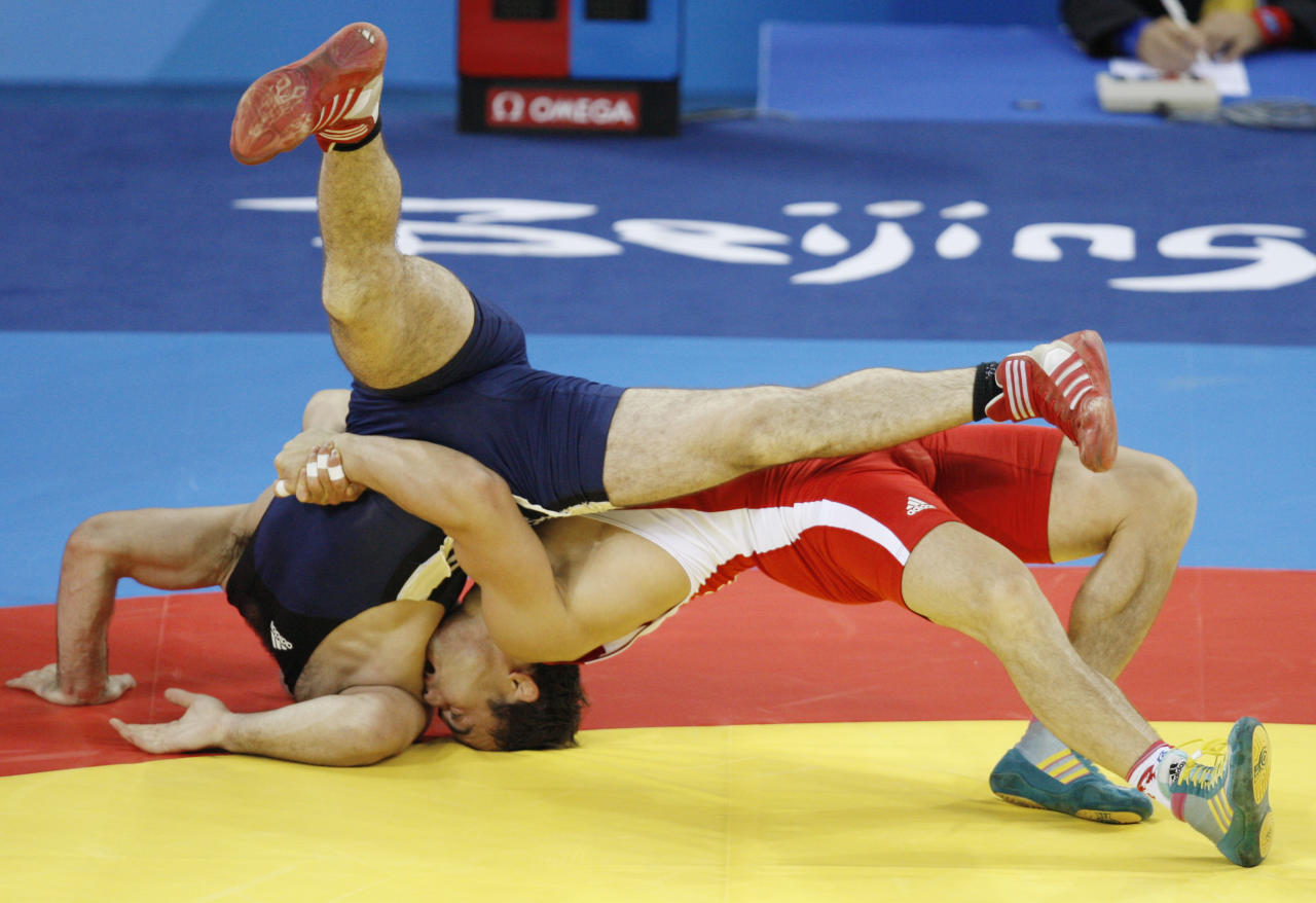 Irbek Ferniev, of Russia, in red, wrestles against Suren Markosyan, of Armenia, in the 66 kilogram category of men's freestyle wrestling competition of the Beijing 2008 Olympics in Beijing, Wednesday, Aug. 20, 2008.  (AP Photo/Saurabh Das )