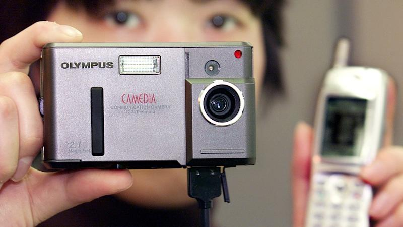 An out-of-focus person holds an Olympus Camedia camera in one hand, an early blocky mobile phone in another, with a cable running between them