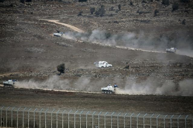 U.N. vehicles drive in Syria, near the border fence with the Israeli-occupied Golan Heights August 31, 2014. The head of the Fijian army said on Sunday negotiations for the release of 44 soldiers seized by an al Qaeda-linked group on the Syrian side of the Golan Heights were being pursued but he worried there had been no word on where his men are being held. REUTERS/Baz Ratner (SYRIA - Tags: CIVIL UNREST POLITICS CONFLICT TPX IMAGES OF THE DAY)