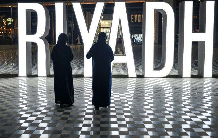 "Women stand before a lit ""I LOVE RIYADH"" sign at a shopping centre in Saudi Arabia's capital Riyadh on October 31, 2020"