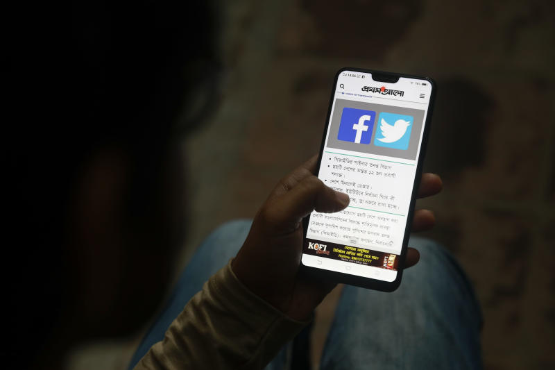 File Photo: A Bangladeshi reads a news report that makes mention of Facebook along with other social networking service, on his mobile phone in Dhaka, Bangladesh, Thursday, Dec. 20, 2018. (AP Photo)