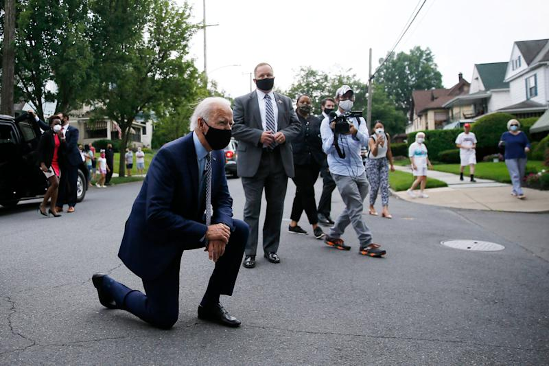Democratic presidential candidate, former Vice President Joe Biden kneels to talk with a child during a visit to Biden's childhood home in Scranton, Pa., on Thursday, July 9, 2020. (AP Photo/Matt Slocum)