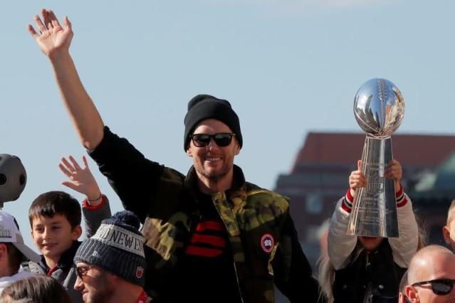 FILE PHOTO: New England Patriots quarterback Tom Brady waves as his daughter Vivian holds up a Lombardi trophy during a victory parade in Boston