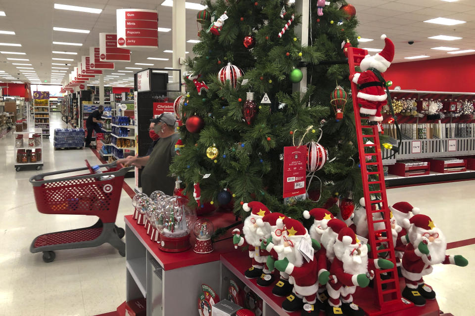 Shoppers walk past a display of Christmas decorations at a Target store, Sunday, Nov. 8, 2020, in Marlborough, Mass. (AP Photo/Bill Sikes)