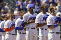 New York Mets relief pitcher Miguel Castro, center, stands for pre-game ceremonies before a home opening baseball game against the Miami Marlins, Thursday, April 8, 2021, in New York. (AP Photo/John Minchillo)