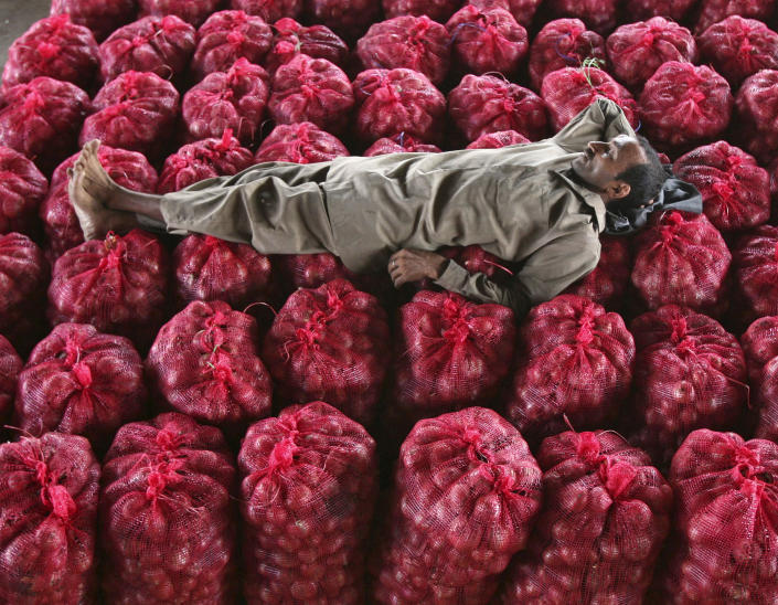 A man takes a nap on sacks filled with onions at a wholesale vegetable market on the outskirts of Jammu September 14, 2011. Indian inflation climbed to its highest in more than a year as prices of food and manufactured goods surged, reinforcing the case for another rate hike on Friday despite weakening growth and a worsening global outlook. (Photo: REUTERS/Mukesh Gupta)