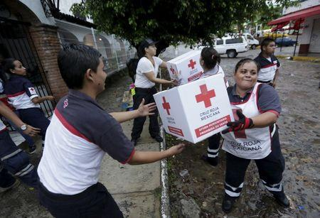 Red Cross volunteers load humanitarian aid boxes from a truck in the Pacific beach resort of Puerto Vallarta