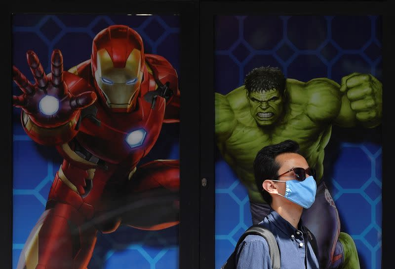 A visitor wears a protective face mask as he queues to enter Madame Tussauds waxworks museum on the first day of its reopening since the easing of lockdown amid the spread of the coronavirus disease (COVID-19), in London