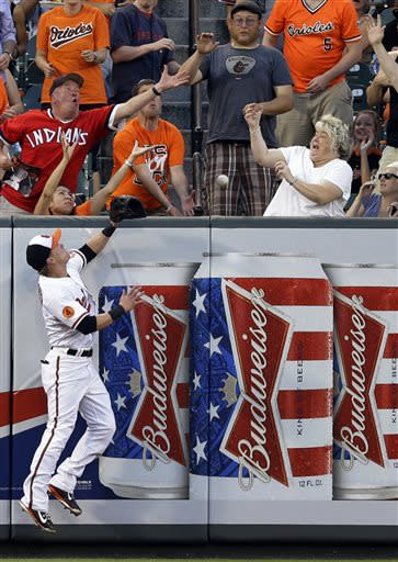 Baltimore Orioles left fielder Nate McLouth, bottom left, and fans reach for a two-run home run by Cleveland Indians' Jason Kipnis in the fifth inning of a baseball game, Tuesday, June 25, 2013, in Baltimore. (AP Photo/Patrick Semansky)
