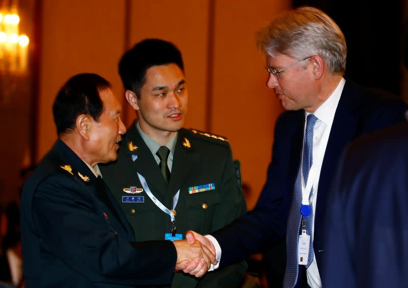 Chinese Defense Minister Wei Fenghe shakes hands with CEO of BAE Systems Charles Woodburn at the the IISS Shangri-la Dialogue in Singapore