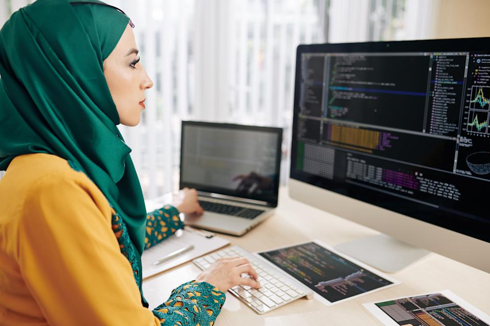 Young muslim coder using computer and laptop when testing new program whe wrote