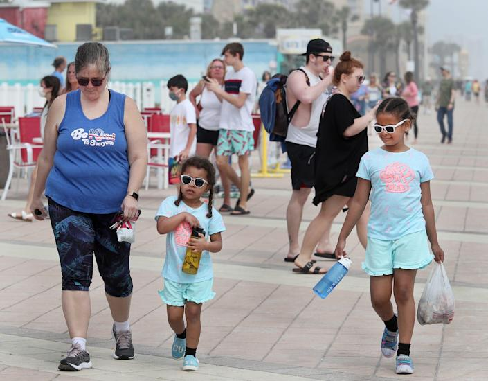 Families and young adults pack the boardwalk on March 23, 2021, as spring break takes a more family turn in Daytona Beach, Fla.