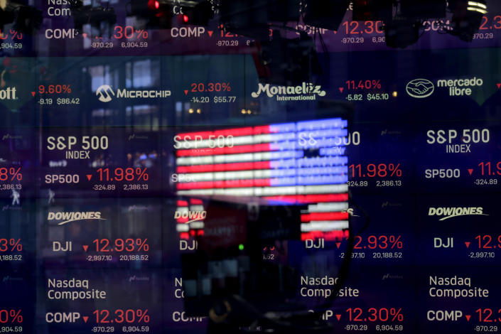 In this March 16, 2020, file photo, United States flag is reflected in the window of the Nasdaq studio, which displays indices and stocks down, in Times Square, New York. (AP Photo/Seth Wenig, File)