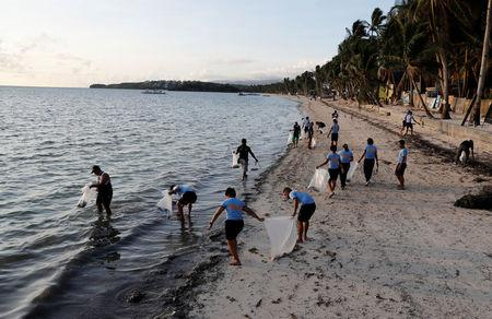 Policemen collect trash at Bulabog beach in the holiday island of Boracay during the first day of a temporary closure for tourists, in Philippines April 26, 2018. REUTERS/Erik De Castro