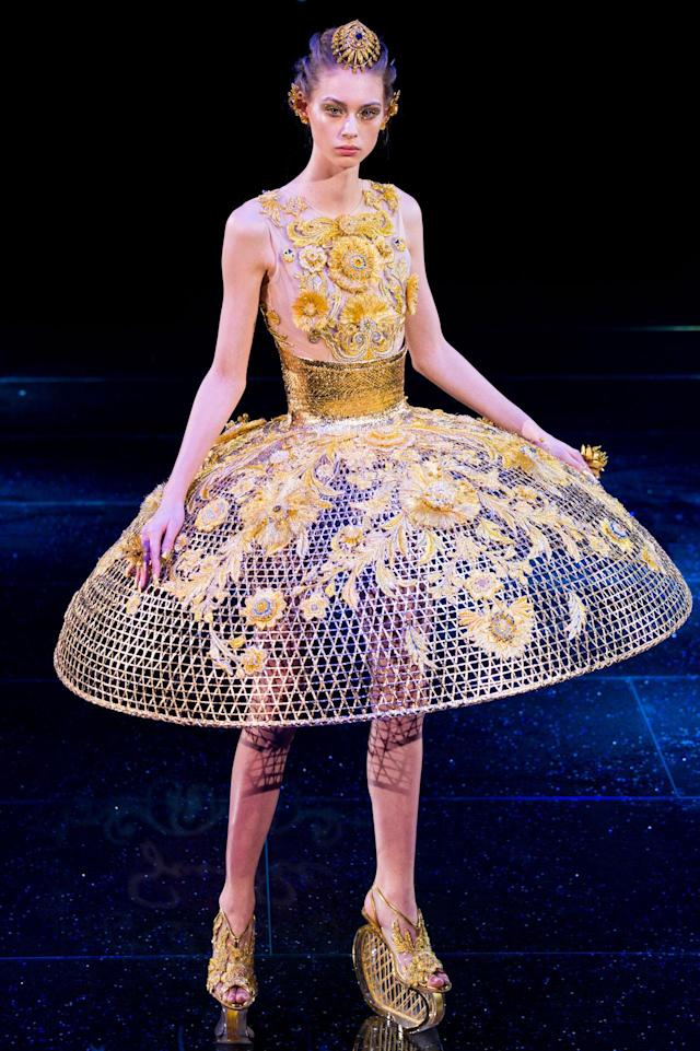 <p>Model wears a yellow-floral embellished dress with a wide cage skirt from the Guo Pei SS18 Haute Couture show. (Photo: Getty Images) </p>