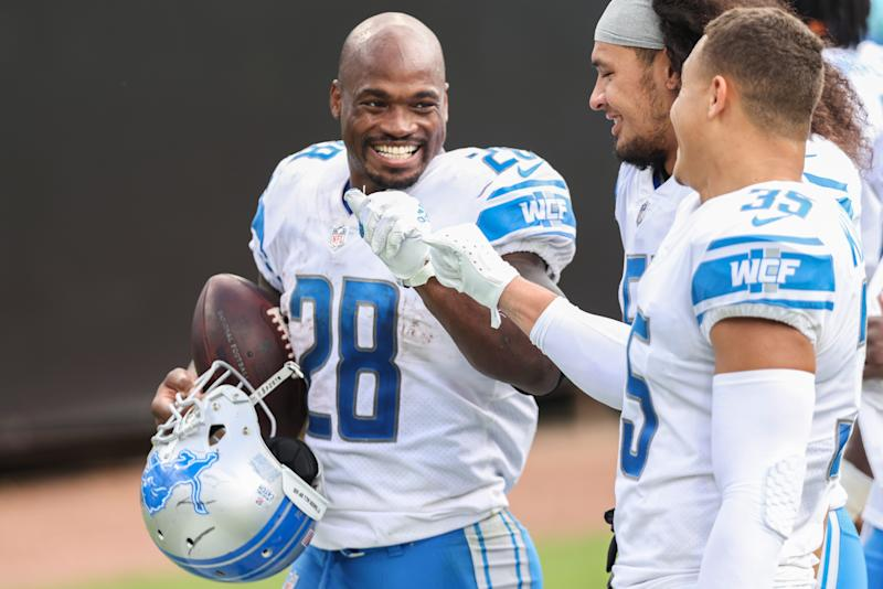 Adrian Peterson (28) of the Detroit Lions celebrates with teammates Miles Killebrew (35) and Jahlani Tavai (51) after defeating the Jacksonville Jaguars 34-16 at TIAA Bank Field on Oct. 18, 2020 in Jacksonville, Florida.