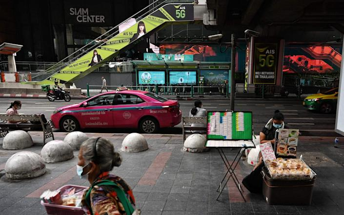 Vendors and commuters around are pictured in the quiet Pathum Wan shopping district in Bangkok on July 11, 2021, a day before stricter lockdown restrictions are brought in to try to contain the spread of the Covid-19 coronavirus - LILLIAN SUWANRUMPHA/AFP