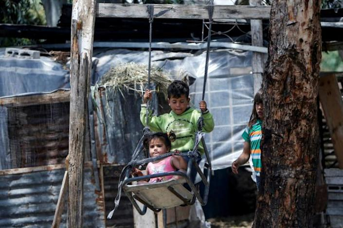 Palestinian children ride on a swing near their home, east of Gaza City (AFP Photo/MOHAMMED ABED)