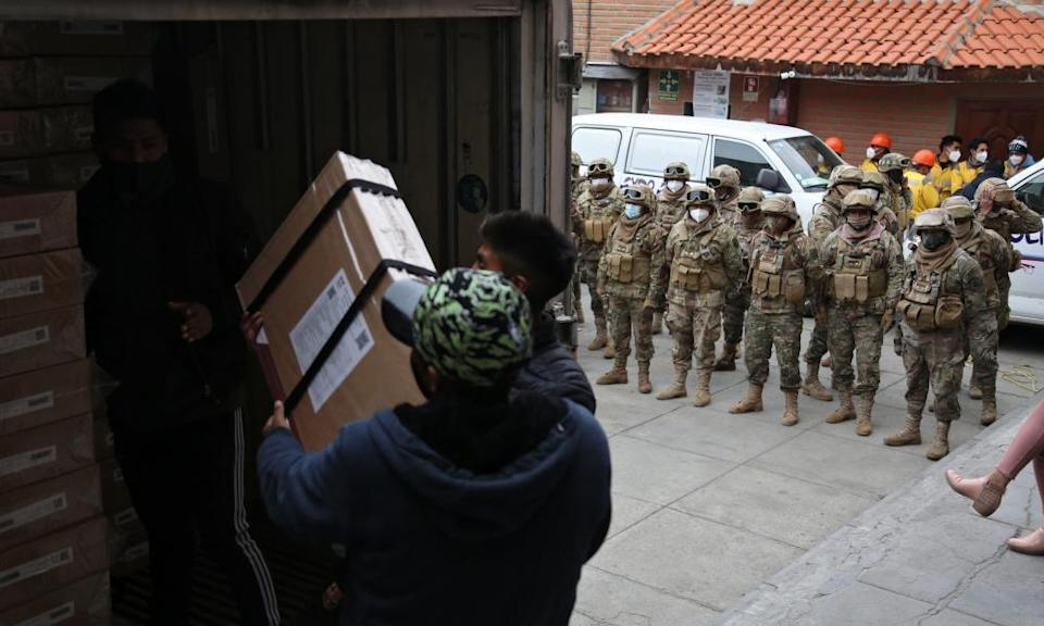 Employees of the electoral court, guarded by the military police, load a truck with electoral material to be distributed for Sunday's general election, in La Paz, on Firday.