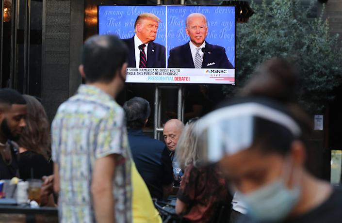 A server wears a face shield and face-covering as people sit to watch a broadcast of the first debate between President Donald Trump and Democratic presidential nominee Joe Biden.