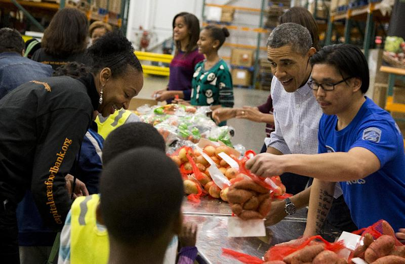 President Barack Obama participates in a Thanksgiving service project by handing out food at the Capital Area Food Bank on Wednesday, Nov. 27, 2013 in Washington. The Capital Area Food Bank distributes 30 million pounds of food annually. (AP Photo/ Evan Vucci)