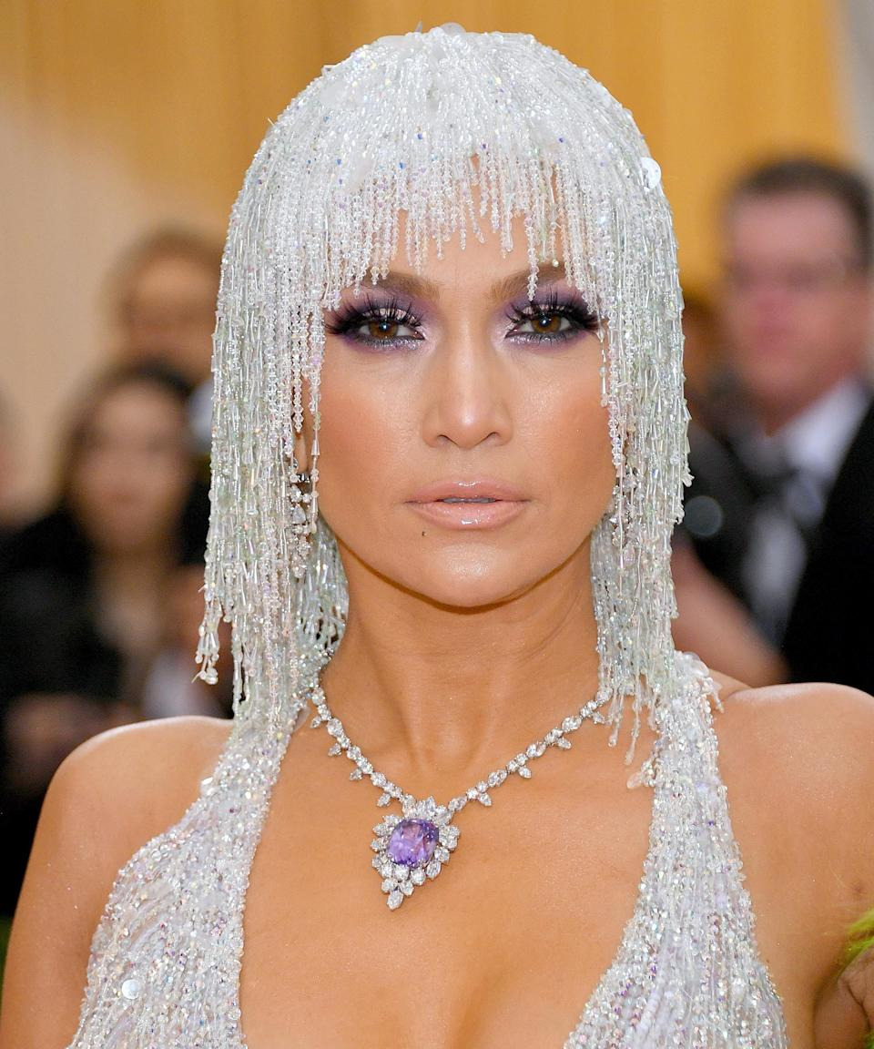 """<h3>2019</h3><br>For the 2019 Met Gala, Lopez hid her hair under a diamond headpiece, allowing her eye makeup to take center stage. Her smoky lavender eyeshadow matched her gigantic neck bezel perfectly.<span class=""""copyright"""">Photo: Dia Dipasupil/FilmMagic.</span>"""