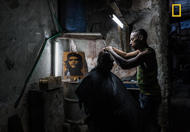 "<p>""This Cuban barber has a shop in the run down building he lives in. He has managed to hook up water and electricity and has a steady flow of clients. I couldn't get enough of the atmosphere and visited the shop several times and each time was welcomed in with a smile."" (© Kelly Beckta/National Geographic Travel Photographer of the Year Contest </p>"