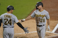 Pittsburgh Pirates' Adam Frazier (26) is greeted by teammate Phillip Evans (24) after scoring off an RBI double by Bryan Reynolds during the third inning of a baseball game against the San Diego Padres, Tuesday, May 4, 2021, in San Diego. (AP Photo/Gregory Bull)