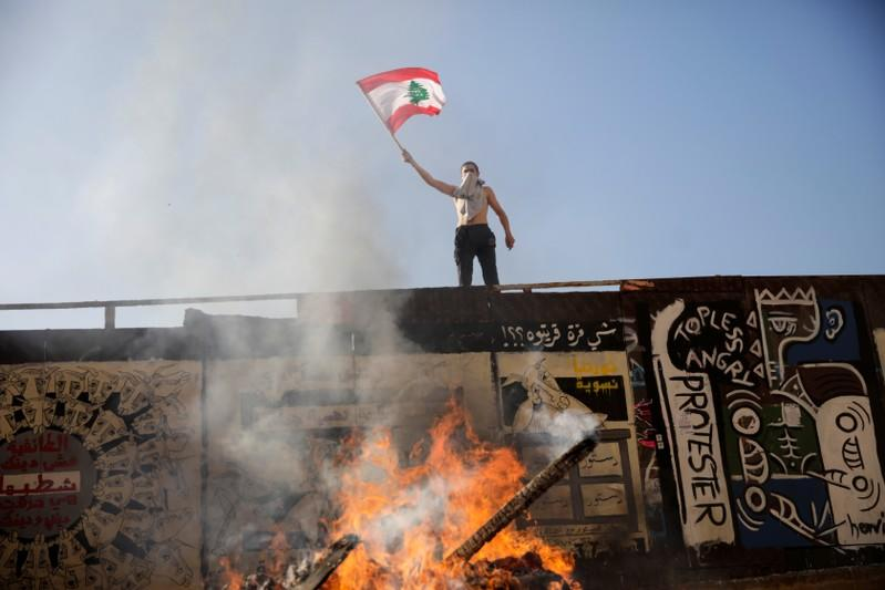 A protester waves a Lebanese flag next to a bonfire during ongoing anti-government protests in Beirut
