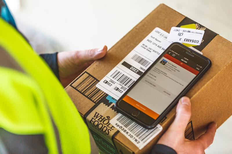 Delivery driver scanning a bar code on a package from Amazon