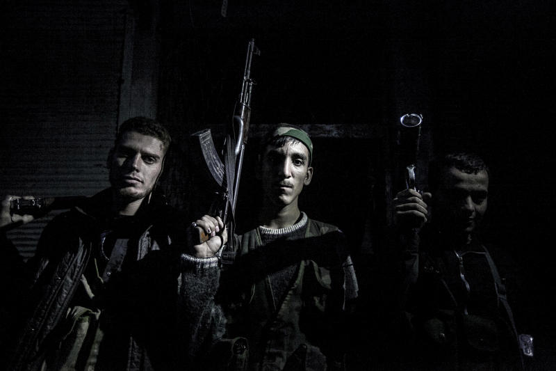 In this Thursday, Oct. 25, 2012 photo, Syrian rebel fighters belonging to the Liwa Al Tawhid unit pose for photo in the Karmal Jabl neighborhood after several days of intense clashes between rebel fighters and the Syrian army in Aleppo, Syria. (AP Photo/Narciso Contreras)
