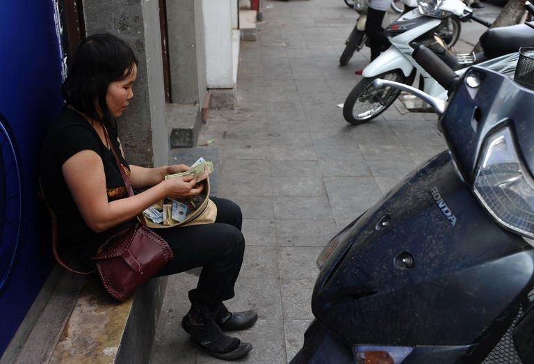 A street vendor counts banknotes on a street in downtown Hanoi, on February 7, 2013