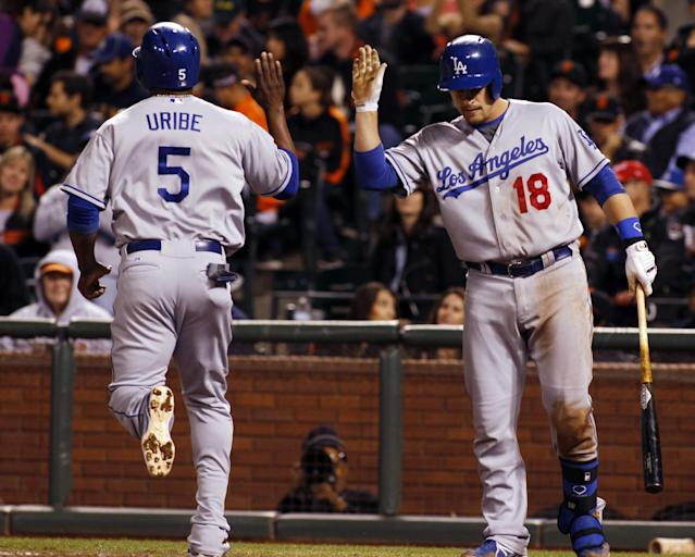 Los Angeles Dodgers' Juan Uribe (5) gets a high-five from teammate Tim Fedorowicz (18) after scoring against the San Francisco Giants during the fourth inning of a baseball game in San Francisco, Thursday, Sept. 26, 2013. (AP Photo/George Nikitin)