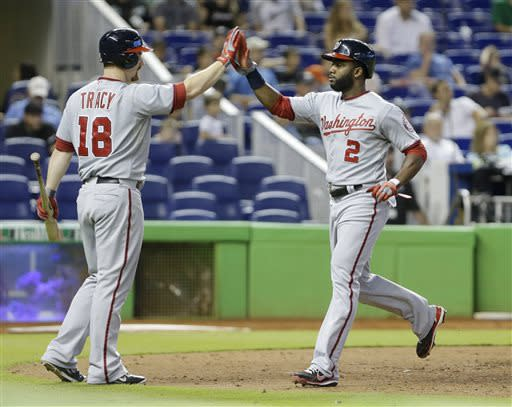 Washington Nationals' Denard Span (2) is congratulated by teammate Chad Tracy (18) after scoring on a single by Wilson Ramos during the 10th inning of a baseball game on Sunday, July 14, 2013, in Miami. The Nationals defeated the Marlins 5-2 in 10 innings. (AP Photo/Wilfredo Lee)