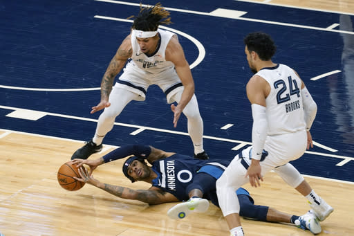Minnesota Timberwolves' D'Angelo Russell (0) tries to grab the ball after falling while double-teamed by Memphis Grizzlies' Brandon Clarke and Dillon Brooks in the first half of an NBA basketball game, Wednesday, Jan. 13, 2021, in Minneapolis. (AP Photo/Jim Mone)