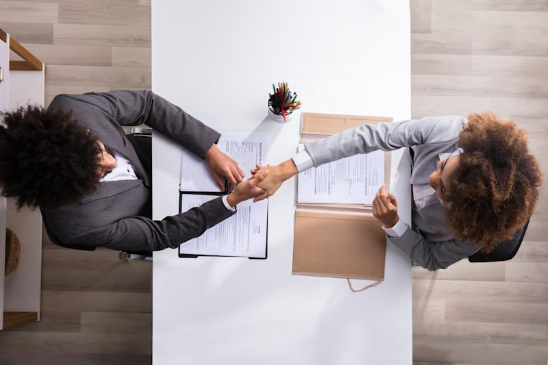 An overhead shot of a business manager and job applicant shaking hands.