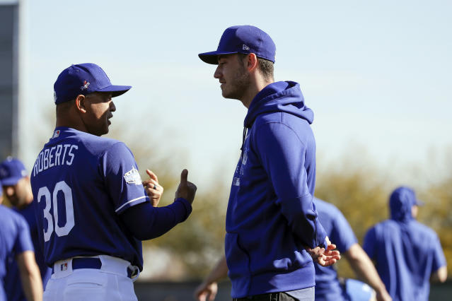 Los Angeles Dodgers manager Dave Roberts, left, talks with center fielder Cody Bellinger during spring training baseball Friday, Feb. 14, 2020, in Phoenix. (AP Photo/Gregory Bull)