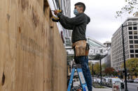 Ahead of the presidential election, a worker boards up a Pret A Manger restaurant along K Street NW, Friday, Oct. 30, 2020, in downtown Washington not far from the White House. (AP Photo/Jacquelyn Martin)