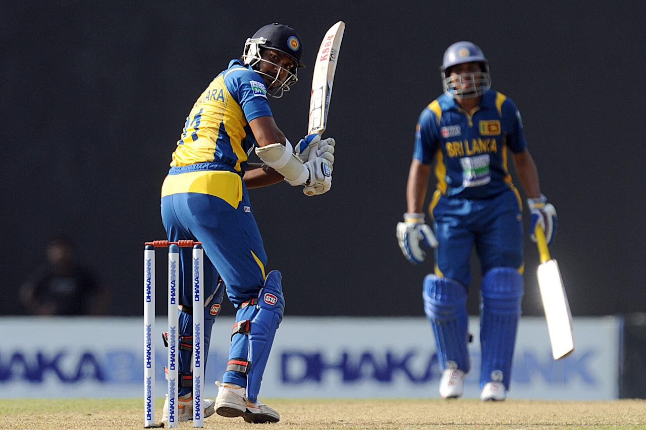 Sri Lankan cricketer Kumar Sangakkara (L) plays a shot as Tillakaratne Dilshan looks on during the third and final one-day international (ODI) match between Sri Lanka and Bangladesh at The  Pallekele International Cricket Stadium in Pallekele on March 28, 2013. AFP PHOTO/ Ishara S. KODIKARA        (Photo credit should read Ishara S.KODIKARA/AFP/Getty Images)