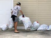 In this April 2021 photo provided by Maria Price, Genshu Price collects recyclable cans and bottles for his fundraiser, Bottles4College, in Hau'ula, Hawaii. Price started Bottles4College three years ago to raise money for his own tuition but has since expanded the recycling project to benefit other students. (Bottles4College via AP)