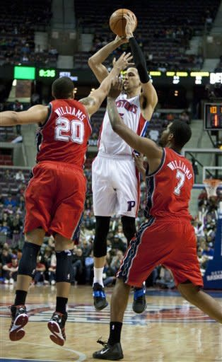 Detroit Pistons' Austin Daye, center, takes a shot against New Jersey Nets' Jordan Williams (20) and Shawne Williams (7) in the second half of an NBA basketball game Friday, Feb. 10, 2012, in Auburn Hills, Mich. The Pistons defeated the Nets 109-92. (AP Photo/Duane Burleson)