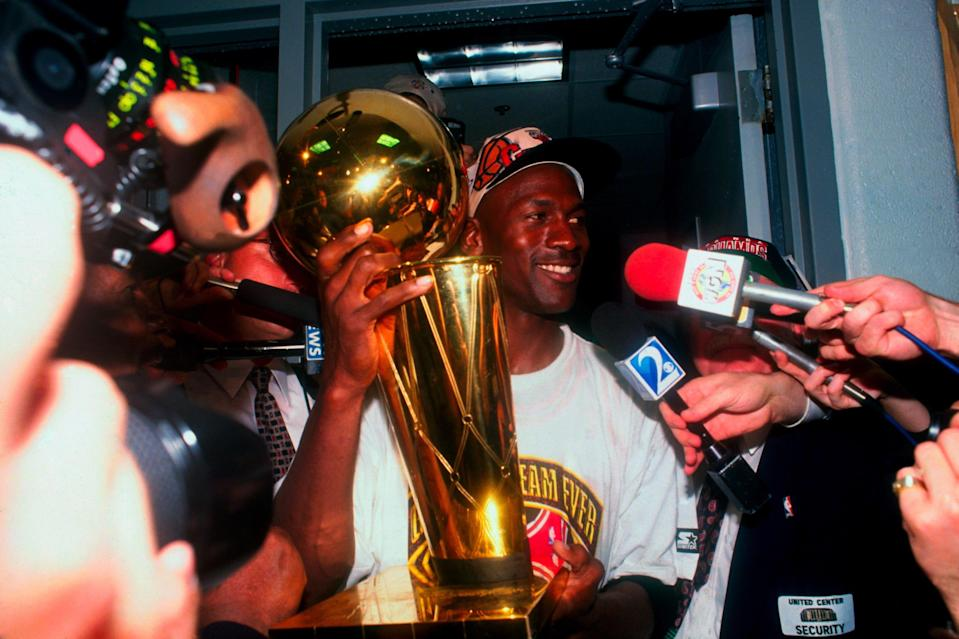 Michael Jordan holds the Larry O'Brien championship trophy after defeating the Seattle Super Sonics in the 1996 NBA Finals at The United Center on June 16, 1996 in Chicago, Illinois. (Getty)