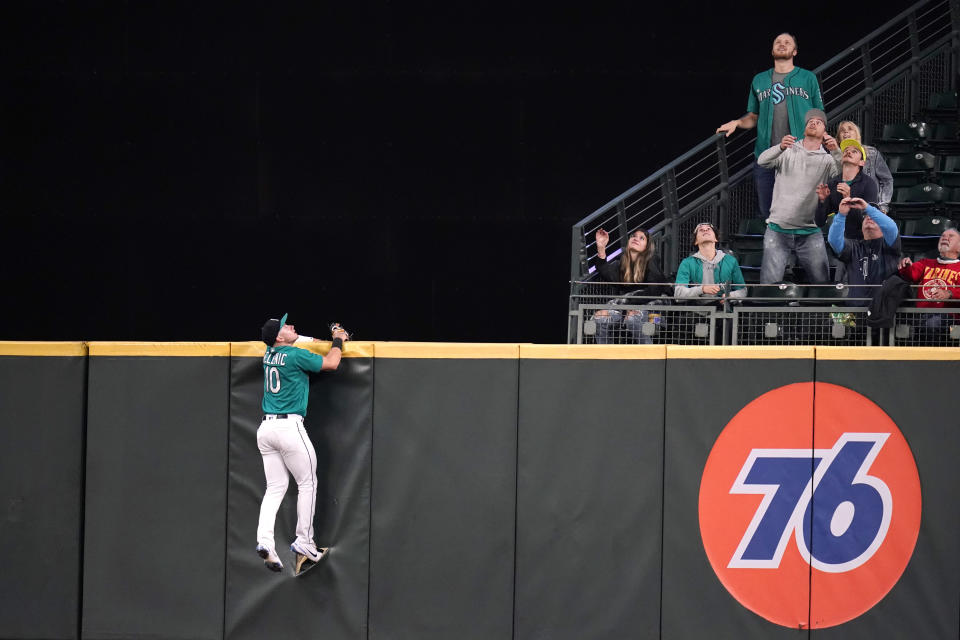 Seattle Mariners center fielder Jarred Kelenic hangs on the outfield fence as he and fans watch a grand slam from Kansas City Royals' Salvador Perez during the fourth inning of a baseball game Friday, Aug. 27, 2021, in Seattle. (AP Photo/Elaine Thompson)