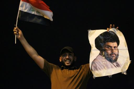 An Iraqi man celebrates with a picture of Shiite cleric Muqtada Sadr during the general election in Baghdad on May 14, 2018